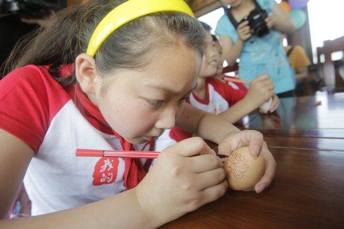 小学生 东湖/小学生聚精会神的创作自己的蛋壳画