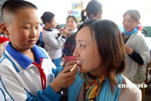 沟镇实验小学,学生们为自己的妈妈梳妆打扮.作者:龚辉(图片来