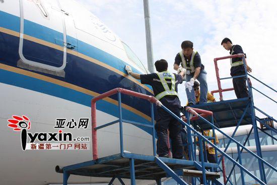 工作人员正在维修被撞的飞机.(亚心网 记者 张军 摄)