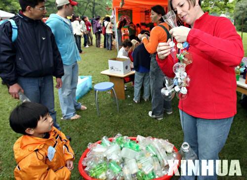 4月22日,一名儿童好奇地观看用废旧饮料瓶制作玩具的过程.